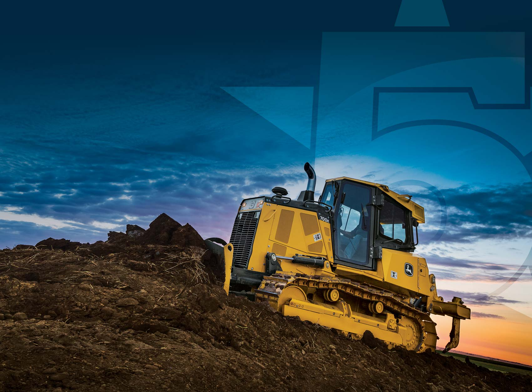 John Deere heavy equipment being used to push earth uphill at sunset
